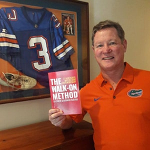 Bobby Raymond holds a copy of the book 'The Walk on Method' in front of his framed University of Florida football jersey.