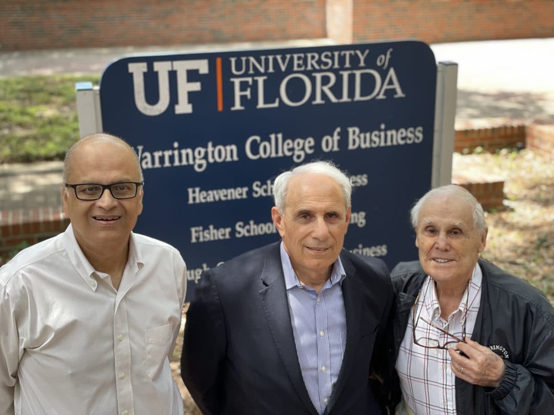 Saby Mitra, John Kraft and Robert Lanzillotti pose for a photo in front of the Warrington College of Business sign.