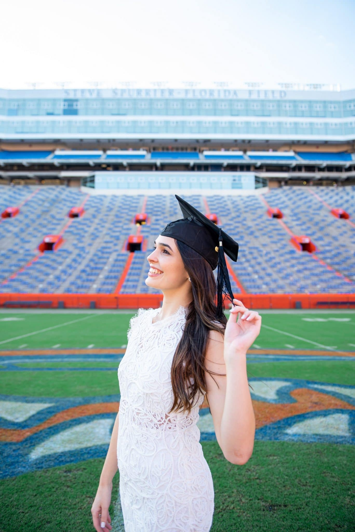 Sandra Cardenal poses for a photo in Ben Hill Griffin Stadium in her graduation cap