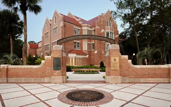 University of Florida entrance with archway and view of Heavener Hall in the background.