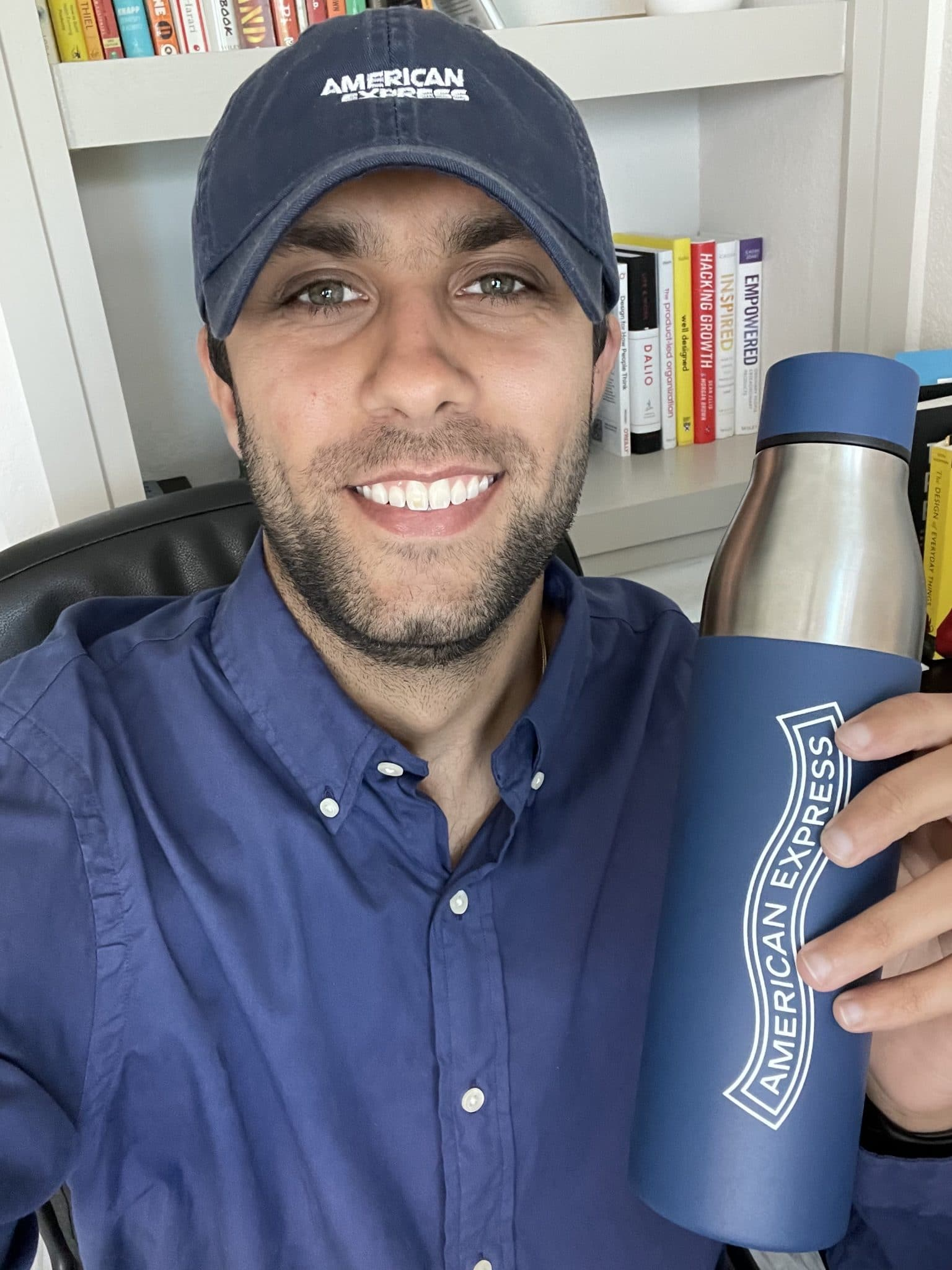 Alexander Chopra takes a selfie wearing an American Express baseball hat and holds an American Express water bottle