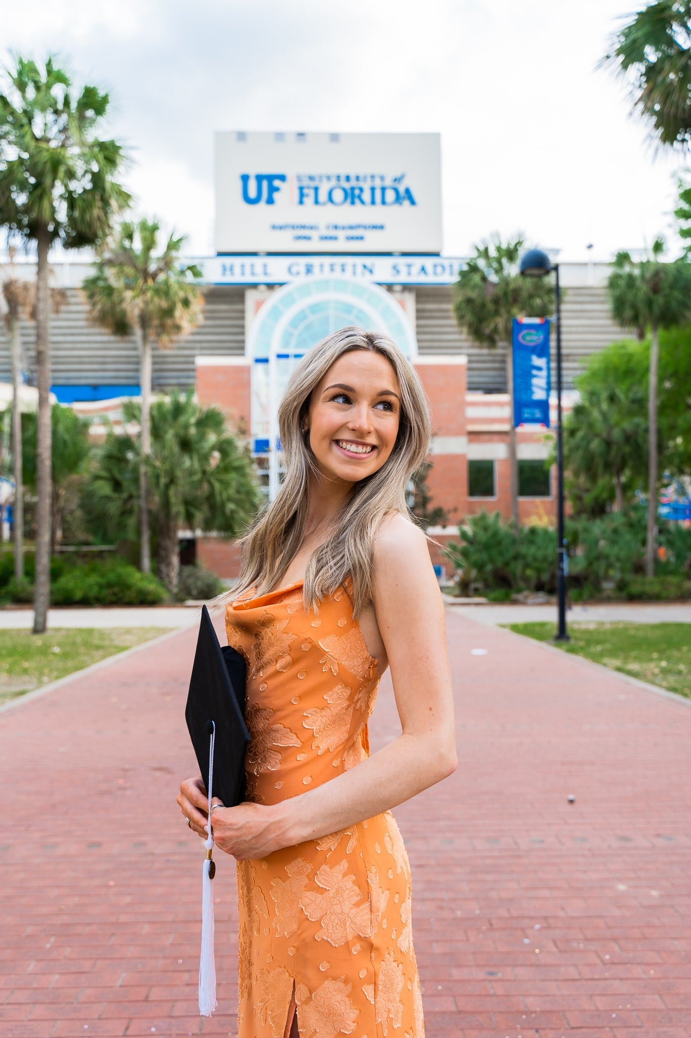 Athena Nolan poses with her graduation cap in front of Ben Hill Griffin Stadium.