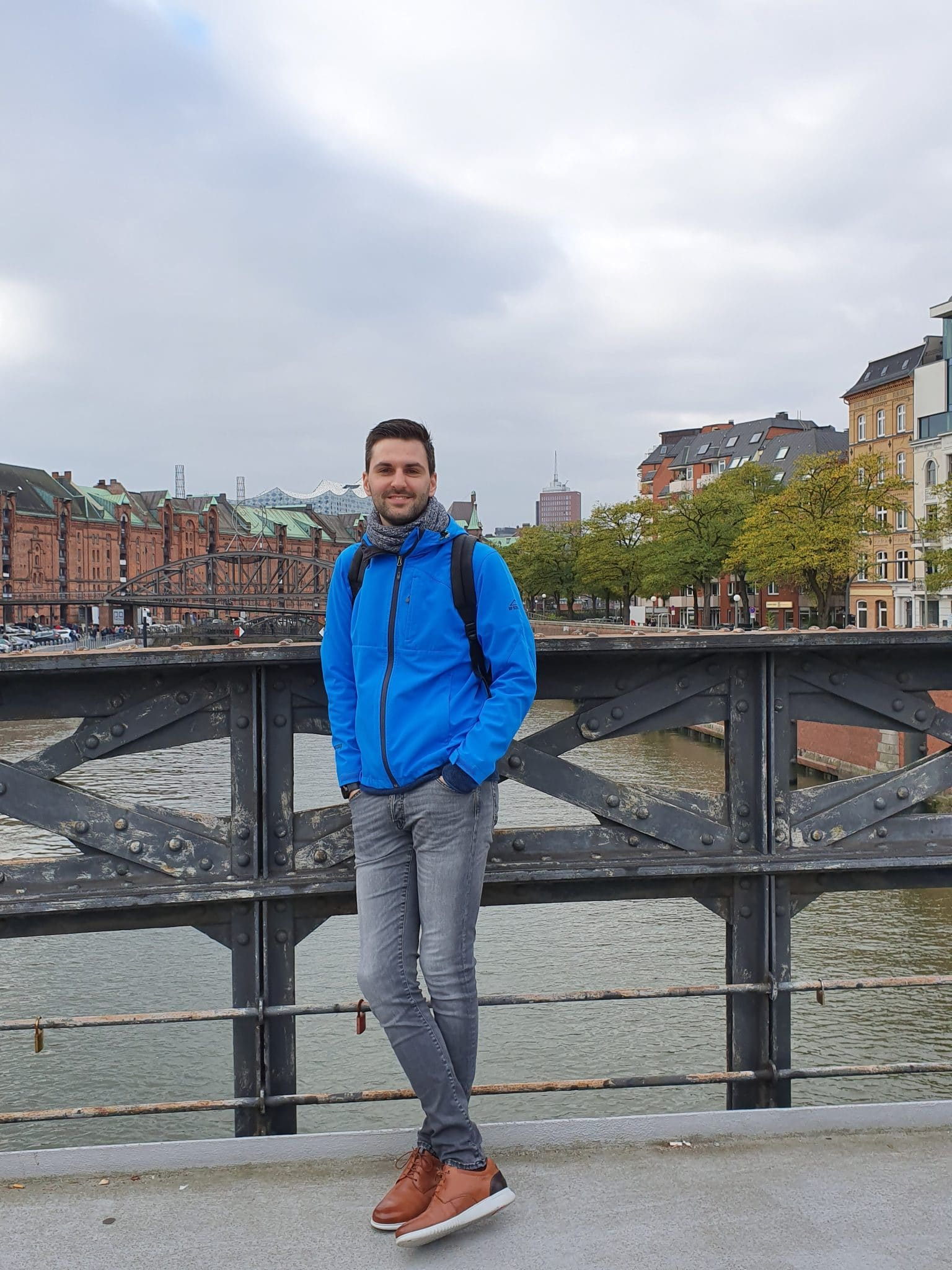 Dominik Vinke poses for a photo on a bridge in a city in Europe.