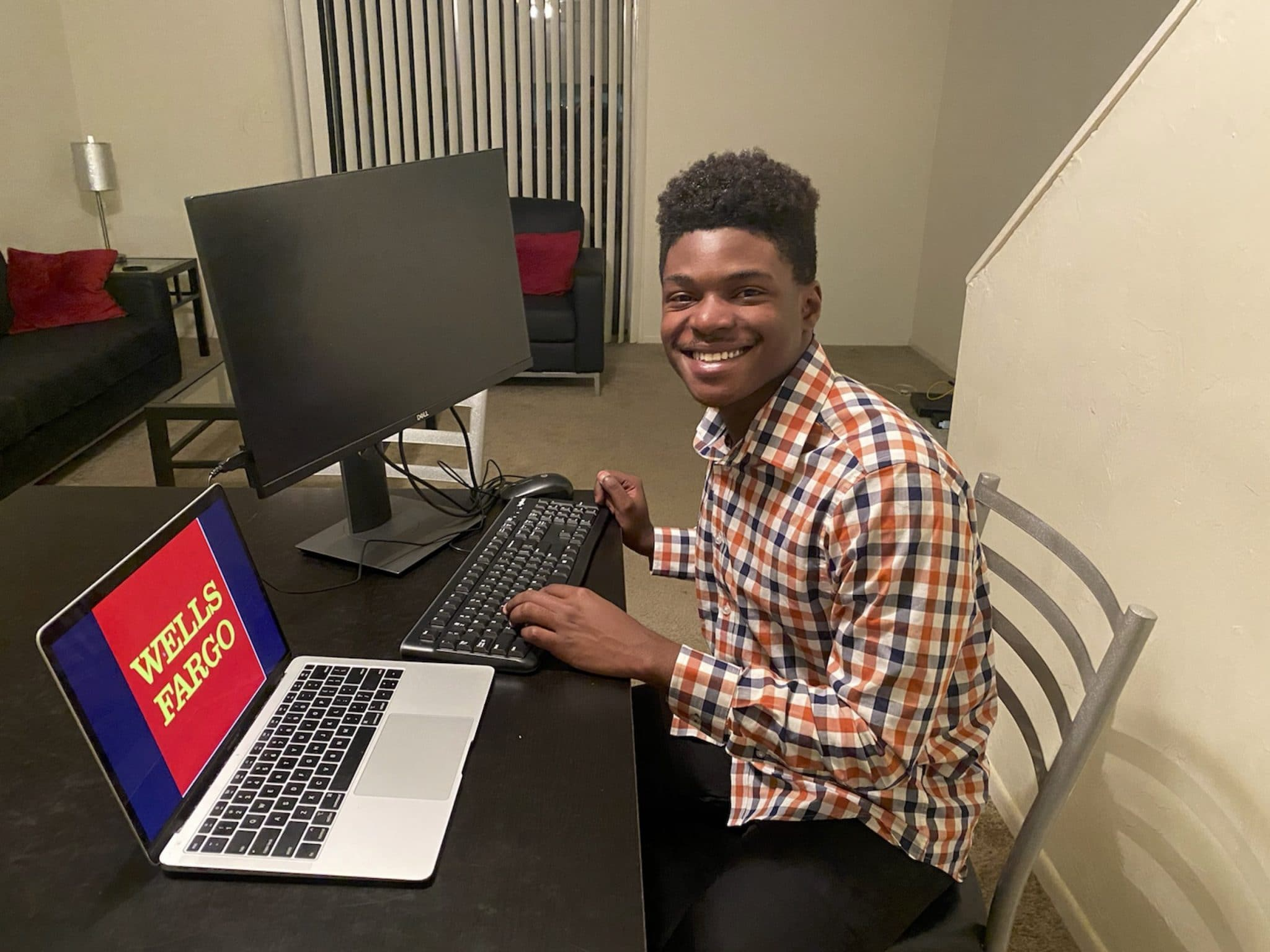 Dwayne Thewell poses for a photo at his home work set up with a laptop and computer monitor with the Wells Fargo logo