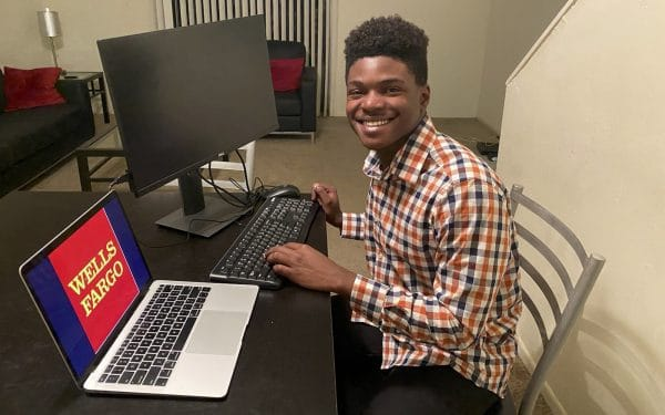 Dwayne Thelwell poses for a photo at his home work set up with a laptop and computer monitor with the Wells Fargo logo