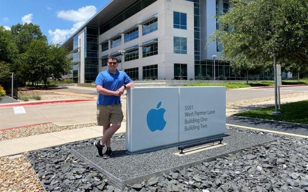Emerson Cardoso poses for a photo by the Apple sign in front of its office building in Texas.