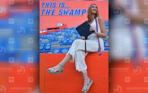 """Julia Yanowitz sits on the edge of a rail between the stands and field at Ben Hill Griffin Stadium holding her graduation cap with text """"This is...The Swamp"""" in the background."""