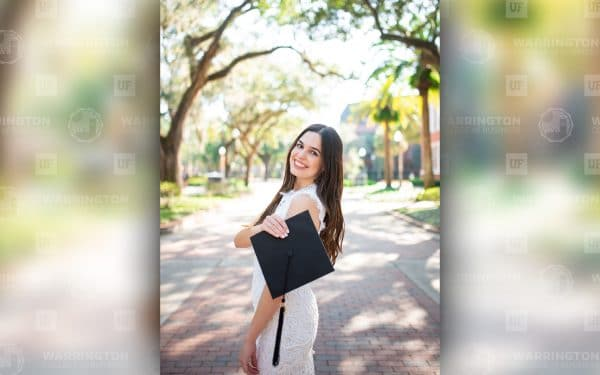 Sandra Cardenal poses on UF's campus with her graduation cap