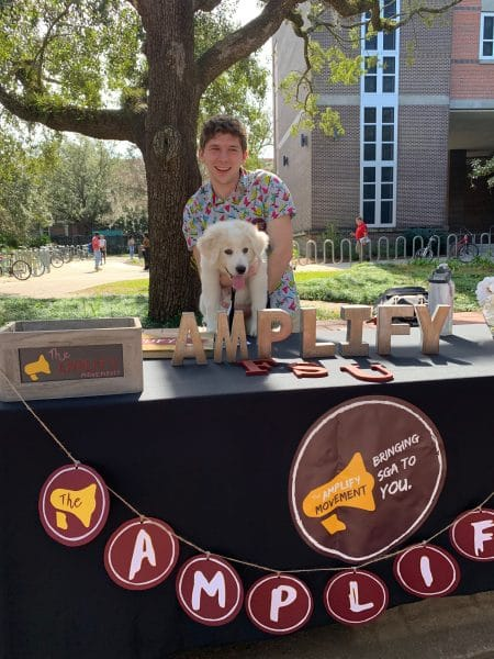 Thomas Driscoll poses for a photo with a puppy while tabling at an event at FSU.