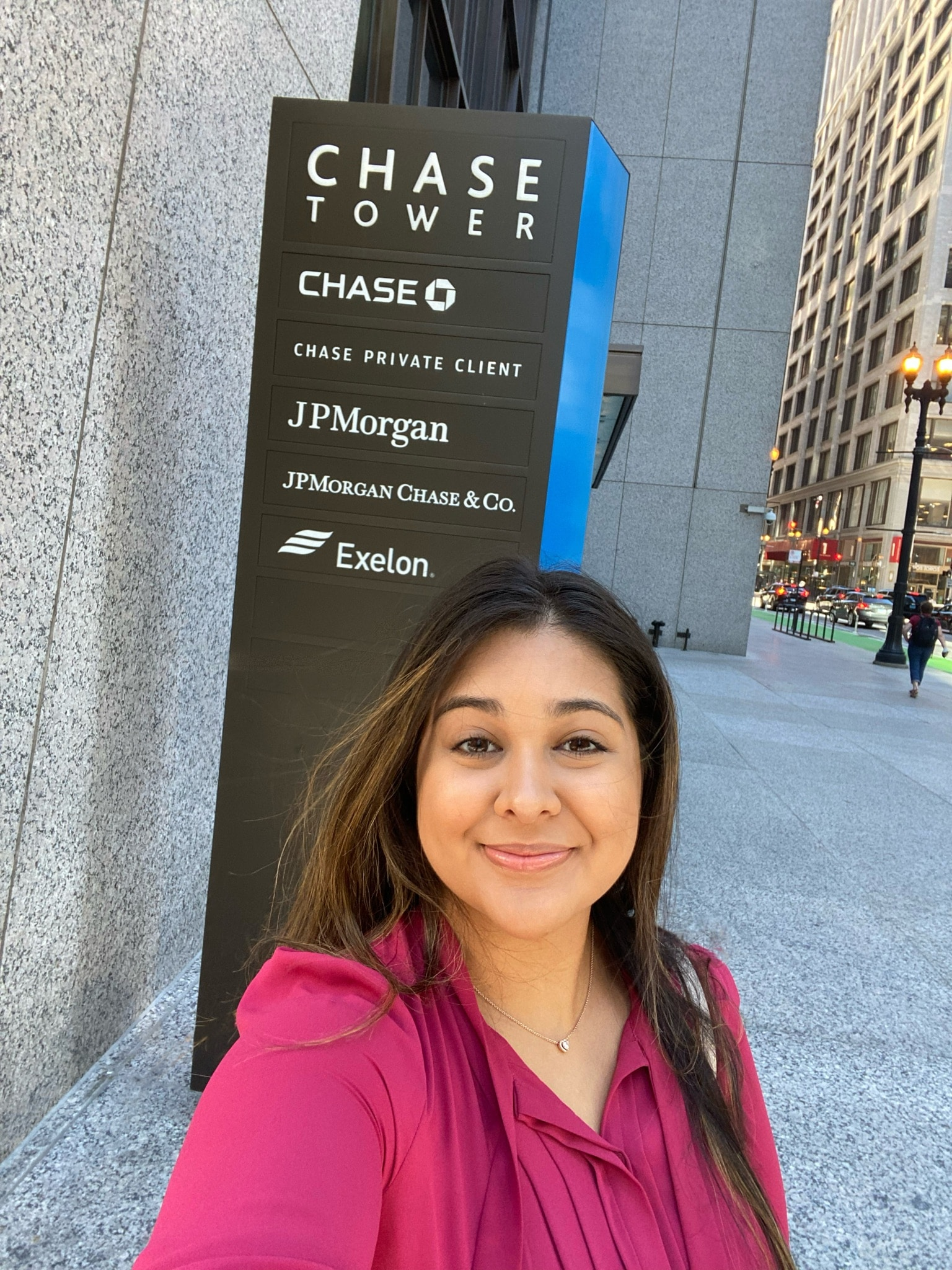 Ysa Moran-Adames takes a selfie in front of the Chase Tower building sign in Chicago.