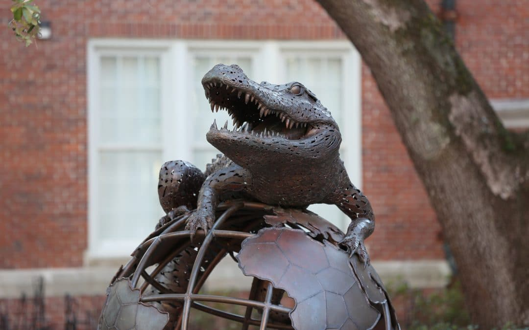 Bronze statue of an alligator sitting on top of a globe.