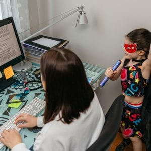 Top view of woman working from home with her daughter singing and playing by her side. Selective focus on girl in background