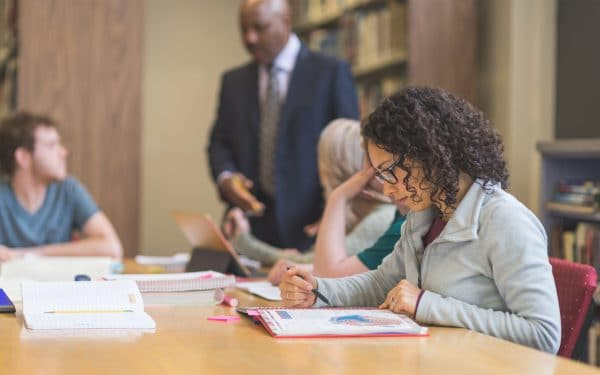 Student does homework at table with classmates and professor