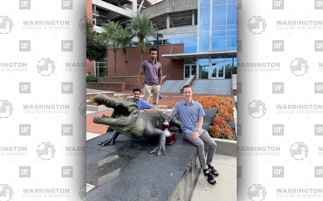 Three young men pose next to a bronze Gator statue with a trophy.