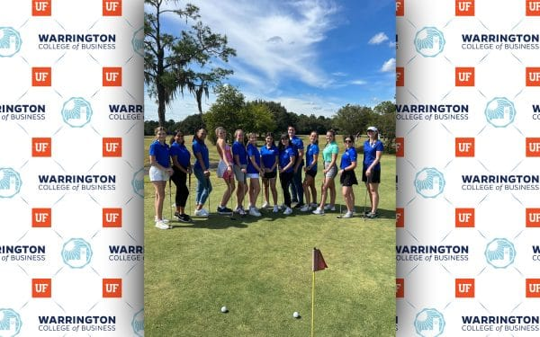 Group of young women posing for a photo on a golf course on a sunny day